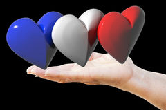 Hand holds french, english, american flag hearts Stock Image