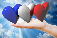 Hand holds french, english, american flag hearts Stock Images