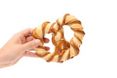 Hand holds freshly fancy pretzel baked. Close up. White background Royalty Free Stock Photography