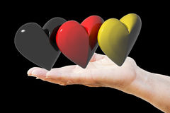 Hand holds german hearts. Hand holds three hearts with the colors of the german flag royalty free stock photos