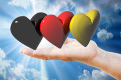 Hand holds german hearts. Hand holds three hearts with the colors of the german flag stock photo