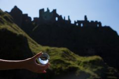 Glass ball in hand, ruins of old irish castle behind, Dunluc Royalty Free Stock Image