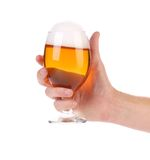Hand holds glass of beer. Royalty Free Stock Photo