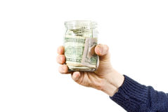Hand holds glass jar with the money Stock Photos