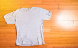 Hand holds a grey t-shirt on a hanger on a white background. Hand holds a grey t-shirt on a hanger on a white Royalty Free Stock Photo