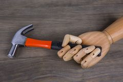 Hand holds a hammer. On a wooden background Royalty Free Stock Photography