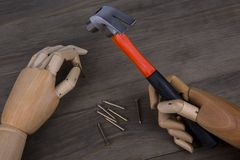 Hand holds a hammer. On a wooden background royalty free stock images
