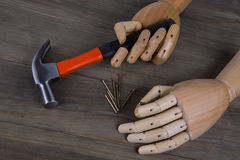 Hand holds a hammer. On a wooden background Stock Photo