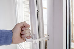 The hand holds the handle of window with restrictor Royalty Free Stock Photography