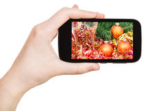 Hand holds handphone with Xmas still life Stock Photography