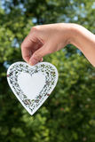 Hand holds hanging heart made of white metal in a park with tree Royalty Free Stock Image