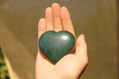 The hand holds the heart from natural stone green jade. Heart in hand. A stone in the shape of a heart. Love talisman, zen, spa.  stock photos