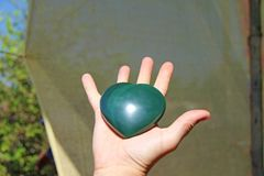 The hand holds the heart from natural stone green jade. Heart in hand. A stone in the shape of a heart. Love talisman, zen, spa.  royalty free stock photos
