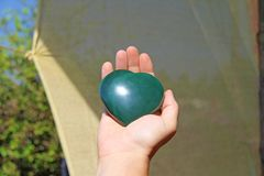 The hand holds the heart from natural stone green jade. Heart in hand. A stone in the shape of a heart. Love talisman, zen, spa