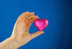 Hand holds a heart shaped gift Royalty Free Stock Image