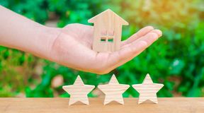 The hand holds the house against the background of three stars. The concept of real estate and property valuation. Survey of hotel stock images