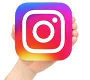 Hand holds Instagram icon on white background. Kiev, Ukraine - January 20, 2017: Hand holds Instagram icon printed on paper. Instagram is an online mobile photo royalty free stock photo