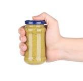 Hand holds italian sauce Pesto. Stock Photos