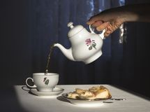 The hand holds the kettle and pours the tea in a cup in the sunlight royalty free stock photos
