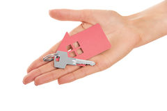 Hand holds key with a keychain the shape of house. Royalty Free Stock Images