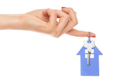 Hand holds key with a keychain the shape of house. Stock Photo