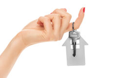 Hand holds key with a keychain the shape of house. Royalty Free Stock Photo