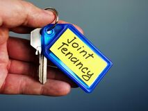 Free Hand Holds Key With Joint Tenancy Inscription Royalty Free Stock Images - 172347589