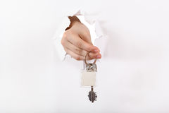 Hand holds the keyring through a hole. In a sheet of paper Stock Photography