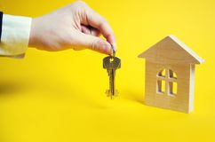 The hand holds the keys on the background of the house. Wooden h royalty free stock photography