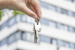 A hand holds the keys to a purchased apartment against the background of a multi-storey building royalty free stock image