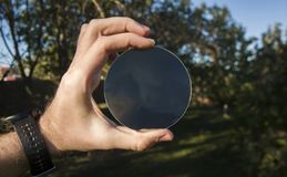 Hand holds a lens on a background of trees stock photos