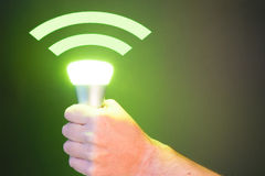 Hand holds a Lifi symbol with bulb. Hand holds a Lifi symbol with glowing bulb combined with wifi symbol Stock Image