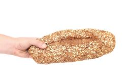 Hand holds a long loaf of bread. Royalty Free Stock Images