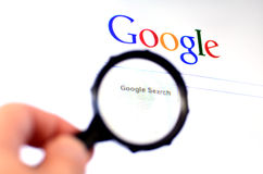 Hand holds Magnifying glass against Google homepage Stock Photo