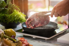 Hand holds meat with tongs. Royalty Free Stock Photos
