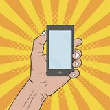 Hand holds a mobile phone. Hand drawn pop art illustration at comic sunburst background with dots halftone effect. Vector Royalty Free Stock Images