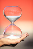 Hand holds a Modern Hourglass. symbol of time. countdown. Modern Hourglass -- sand trickling through the bulbs of a crystal sand glass. symbol of time. countdown Royalty Free Stock Photo