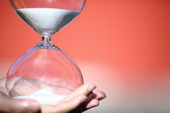 Hand holds a Modern Hourglass. symbol of time. countdown. Modern Hourglass -- sand trickling through the bulbs of a crystal sand glass. symbol of time. countdown Royalty Free Stock Photography