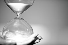 Hand holds a Modern Hourglass. symbol of time. countdown Royalty Free Stock Photography