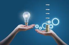Hand holds money, hand holds light bulb. Stock Image