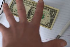 The hand holds the money in the notebook on the desk in the office. A bribe giving. corruption. Dollars for work. work done for mo Royalty Free Stock Photography