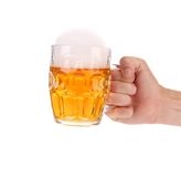 Hand holds mug of beer with foam. Stock Image