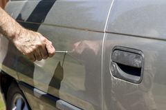 The man holds a nail in his hand and destroys the paint of the car by drawing it. The hand holds the nail and destroys the car`s paint on the door by drawing a royalty free stock images