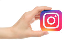 Hand holds new Instagram logo printed on paper. Kiev, Ukraine - May 17, 2016: Hand holds new Instagram logo printed on paper, on white background. Instagram is