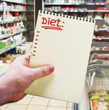 Hand holds a notebook with diet plan Stock Photo