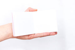 Hand holds notebook open. Blank white paper. Place for an inscription Royalty Free Stock Photos