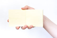Hand holds notebook open. Blank white paper. Place for an inscription Stock Photo
