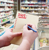 Hand holds a notepad with diet plan Stock Photography