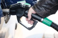 Hand holds a nozzle to refuel a car with diesel fuel at the gaso Royalty Free Stock Images