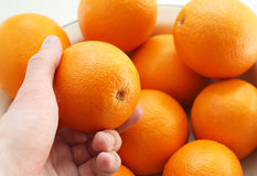 The hand holds an orange Stock Image